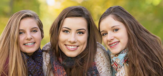 Two young girls with braces smiling next to a young woman with Invisalign