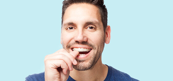A handsome man smiling as he puts on his Invisalign aligner trays