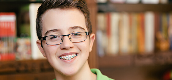 A Young boy with braces smiling in a library