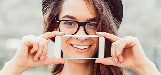 A young woman holding up a phone with a picture of a smile on it over your mouth