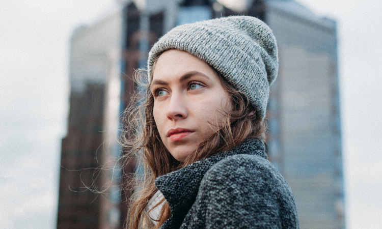 Woman wears a beanie in front of a skyscraper and looks anxiously into the distance wondering about her wisdom teeth