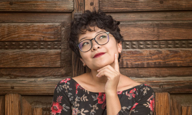 Short-haired brunette young woman wearing glasses puts her hand ponderously under her chin in front of a wooden door
