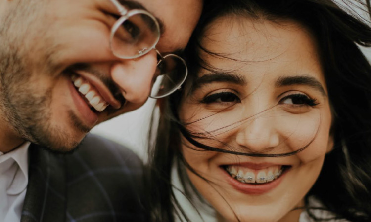 smiling couple displaying metal vs invisalign braces