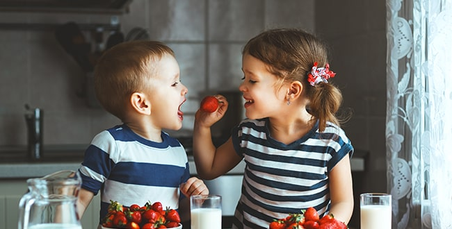Two young siblings enjoying strawberries