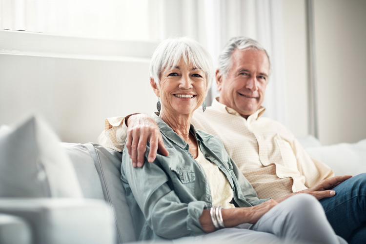 White-haired husband and wife wearing dentures sits companionably on a gray couch smiling