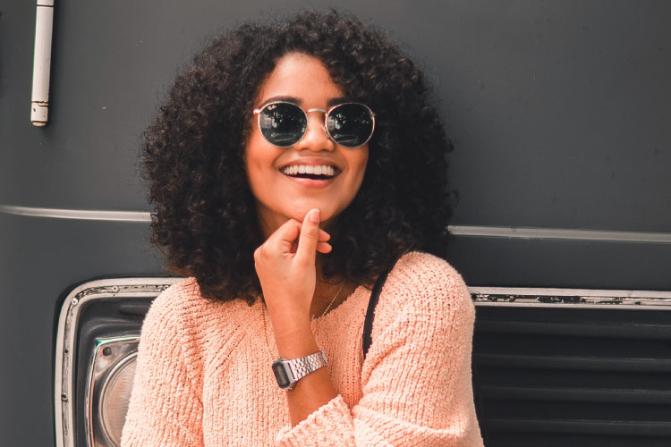 Curly-haired woman wearing sunglasses, silver watch, and a peach sweater smiles with CEREC same-day dental crowns against a gray bus